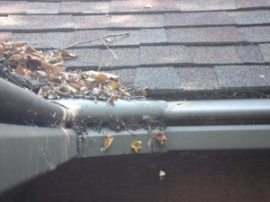 Clogged gutter before and after. Gutter cover being installed